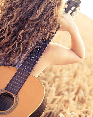 Beautiful young girl carryng her guitar through the golden wheat field. Lens flare, selective focus, toned image.